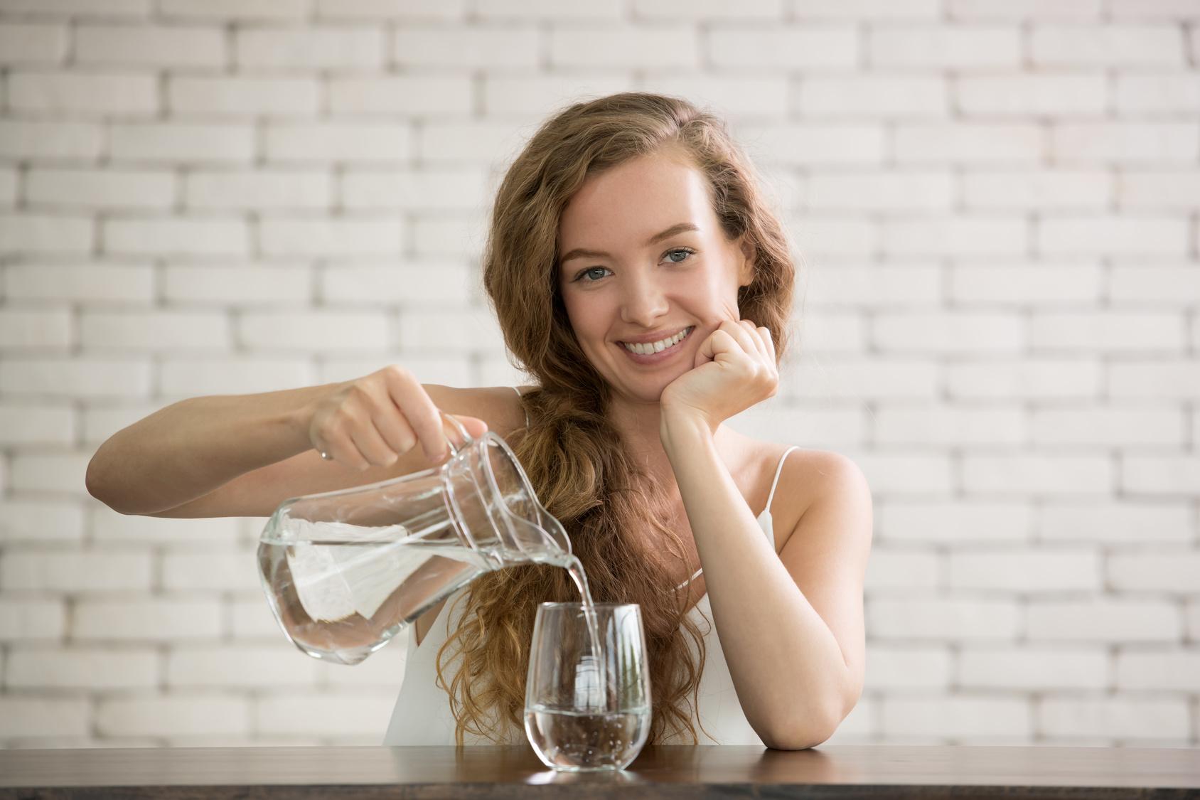 Junge Frau füllt ein Glas mit Wasser
